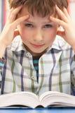 Beklemtoonde Schooljongen die in Klaslokaal bestudeert Stock Foto