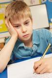 Beklemtoonde Schooljongen die in Klaslokaal bestudeert Stock Afbeelding