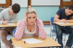 Beklemtoonde studentenzitting in een klaslokaal stock foto