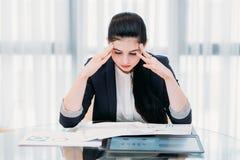 Beklemtoonde vermoeide bureau bedrijfsvrouwen hoofdhanden stock afbeelding