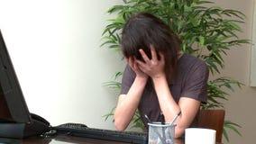 Beklemtoonde vrouw die bij een computer werken stock footage
