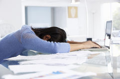Beklemtoonde Vrouw die bij Laptop in Huisbureau werken Stock Foto's