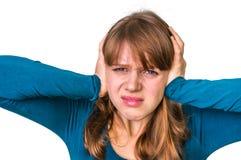 Beklemtoonde vrouw die haar oren tegen hevig lawaai behandelen te beschermen stock fotografie