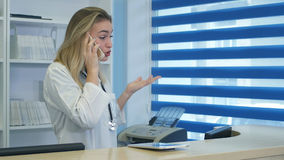 Beklemtoonde vrouwelijke medische arbeider die terwijl het spreken op telefoon bij het ziekenhuisontvangst schreeuwen Stock Foto
