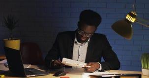 Beklemtoonde zakenman die in documenten per ongeluk wordt verward die bij bureau in nachtbureau werken : stock videobeelden
