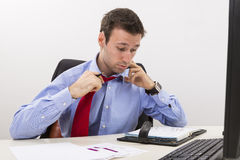 Beklemtoonde zakenman die een harde dag hebben op kantoor Stock Afbeelding