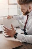 Beklemtoonde zakenman die met documenten en omslagen bij lijst in bureau zitten Royalty-vrije Stock Fotografie