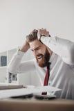Beklemtoonde zakenman die met documenten en omslagen bij lijst in bureau zitten Stock Foto