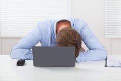 Beklemtoonde zakenman die op bureau leunen Stock Foto's