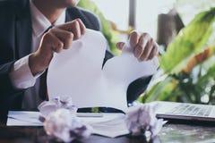 Beklemtoonde zakenman tearing documenten stock foto