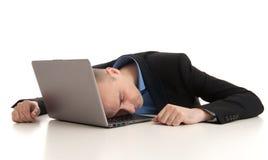 Beklemtoonde zakenmanslaap op laptop stock foto