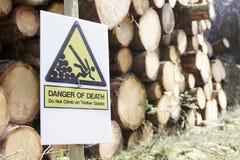 Beklim niet op gehakt houten logboeken gestapeld gevaar van gevaarsteken in bosbossen stock foto's