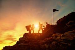 Beklimmen werken de silhouet mannelijke en vrouwelijke wandelaars die op bergklip, Hulp en team concept stock foto