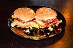 Bekon i chees hamburger na talerzu, zakończenie podnosimy makro- fotografię Zdjęcia Royalty Free