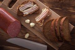 Bekon i kiełbasa z czarnym chlebem i czosnkiem na drewnianym stole zdjęcia royalty free
