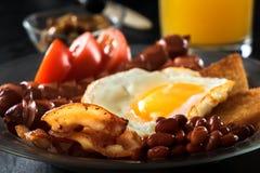 Bekon, piec na grillu kiełbasy, smażący jajko, fasole, fasole, grzanka, pomidory, pieczarka świeży sok - pełny Angielski śniadani Obrazy Royalty Free