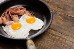 Bekonowy i jajko Solony jajko i kropiący z czarnym pieprzem Angielski śniadanie Piec na grillu bekon, dwa jajka na niecce na drew Zdjęcia Royalty Free