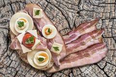 Bekonowy Serowy Jajeczny baleron i Pomidorowa kanapka na Starej beli Obrazy Stock