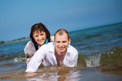 Bekoord mens en meisje die in golven van overzees liggen Stock Foto's