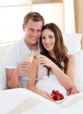 Bekoorde paar het drinken champagne die in bed ligt Stock Foto's