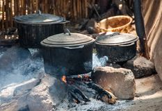 Pots on fire in a malagasy village. Bekopaka, Madagascar - nov 2016 : old pots on the wood fire of a kitchen of the village of Bekopaka in the west of Madagascar stock photo