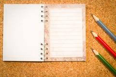 Bekorken Sie Brett mit einem Notizblock und den bunten Bleistiften Stockfoto