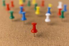 Bekorken Sie Brett mit rotem Mittelstift und Hintergrund blured Stiften Stockfotos