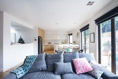Bekväm grå soffa i öppet hem för planvardagsrumsamtida royaltyfri bild