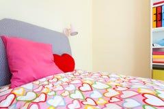 Bekväm säng i liten flickarum Arkivfoto