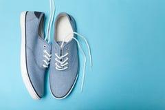 Bekväma blåa gymnastikskor för mjuk sommar på en blå bakgrund Kopiera utrymme f?r text royaltyfria foton