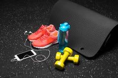 Bekväma sportskor, en flaska av vatten, hantlar och telefon på en svart bakgrund Tillbehör för idrottshallutbildning Arkivfoto