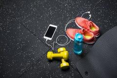 Bekväma sportskor, en flaska av vatten, hantlar och telefon på en svart bakgrund Tillbehör för idrottshallutbildning Royaltyfria Foton