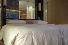Bekväma två sängar i hotell med badrummet till och med exponeringsglasbakgrunden fotografering för bildbyråer
