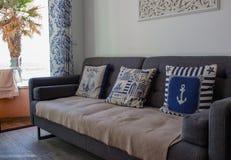 Bekvämt rum med soffan och kuddar Hemtrevlig lägenhet som är inre i blåa färger r royaltyfri bild