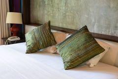 Bekväm säng med dekorativa kuddar Arkivfoto