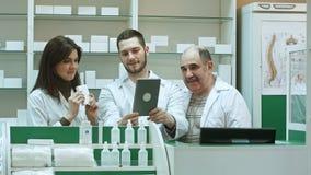 Bekwaam apotheekteam met apotheker en apotheektechnici die videopraatje met collega's hebben die digitale tablet gebruiken stock afbeeldingen