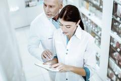 Bekwame apotheker die zijn medewerker helpen tijdens het werk royalty-vrije stock afbeelding