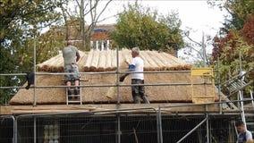 Bekwame dakthatchers die een de theehut met stro bedekken van Kent stock footage