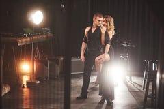 Bekwame dansers die in de donkere ruimte onder het licht presteren Stock Fotografie