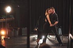 Bekwame dansers die in de donkere ruimte onder het licht presteren Stock Foto's