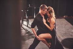Bekwame dansers die in de donkere ruimte onder het licht presteren Stock Afbeeldingen