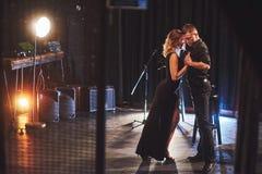 Bekwame dansers die in de donkere ruimte onder het licht presteren Royalty-vrije Stock Foto's
