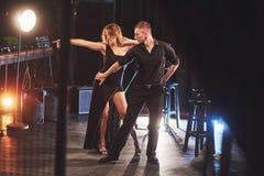 Bekwame dansers die in de donkere ruimte onder het licht presteren Stock Foto