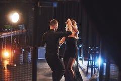 Bekwame dansers die in de donkere ruimte onder het licht presteren Royalty-vrije Stock Foto