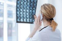 Bekwame dokter die hersenenröntgenstraal in de kliniek bespreken royalty-vrije stock foto