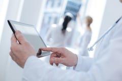 Bekwame dokter die moderne tablet in de kliniek gebruiken royalty-vrije stock foto