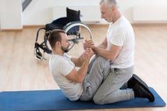 Bekwame huisarts die de gehandicapten bijstaan in de gymnastiek stock fotografie