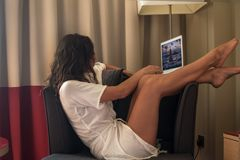 Bekwame jonge vrouw in moderne luxeflat, zitten comfortabel in de computer van de leunstoelholding op haar overlappingen, het ont stock foto's