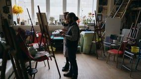 Bekwame kunstenaarsmens die jong meisje onderwijzen om schilderijen te trekken en de grondbeginselen in kunst-klasse verklaren Stock Afbeelding