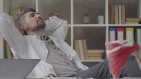 Bekwame mannelijke artsen die röntgenstraal in het bureau van moderne kliniek controleren Jonge mens die in witte robe x-ray zitt stock video